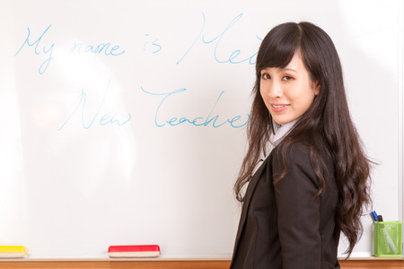 Chinese female teacher writing name on whiteboard for first day of school photo