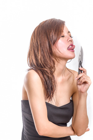 femme fatale: Chinese woman in a black dress about to lick a  knife