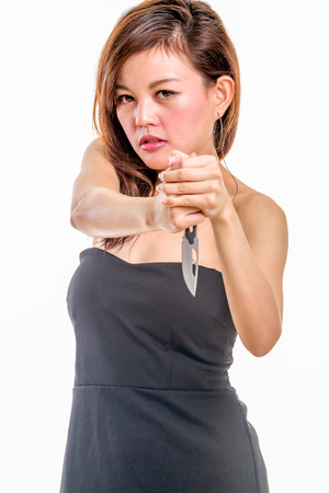 femme fatale: Chinese woman in a black dress holding a  knife in stabbing pose