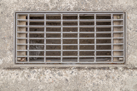 sewer: Sewer cover or storm drain in street