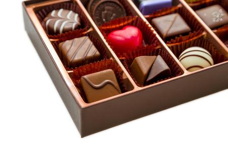 Verschiedene Pralinen in braunen Kasten, mit rotem Herz Schokolade Standard-Bild - 36173343