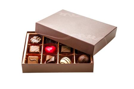 golosinas: Chocolates surtidos en caja marrón, con media tapa Foto de archivo