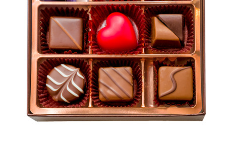 Assorted chocolates in brown box, with red heart chocolate Foto de archivo