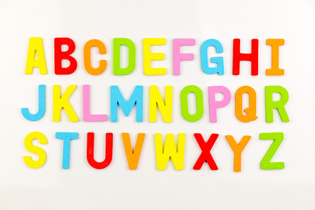 nevera: Imanes coloridos del alfabeto en la pizarra blanca