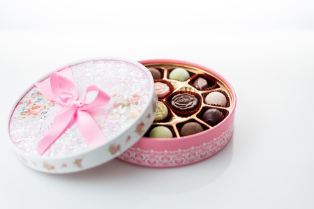 fancy sweet box: Pink box of chocolates with ribbon on white background Stock Photo