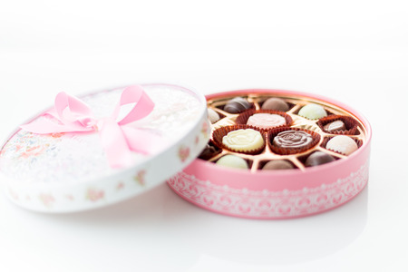 fancy box: Pink box of chocolates with ribbon on white background Stock Photo