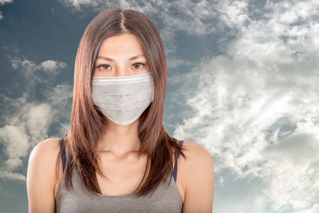 Chinese woman wearing surgical mask with cloudy sky in background