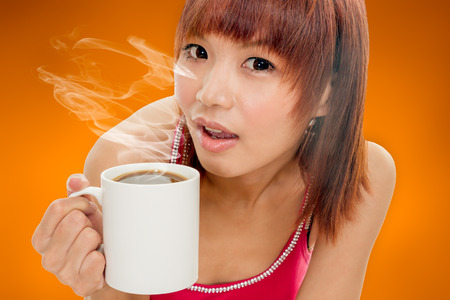 Chinese woman holding a steaming mug of coffee photo