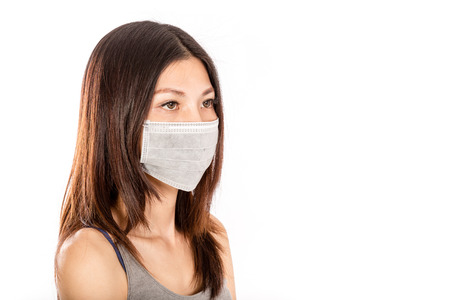Chinese woman wearing surgical mask looking away, with white background