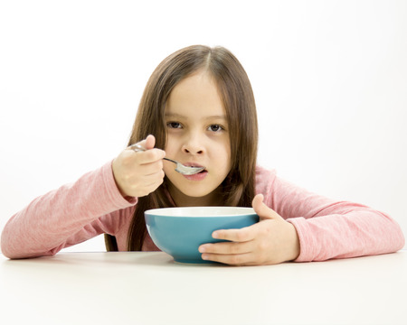 Young girl eating her morning bowl of cereal