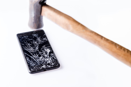 hit tech: Hammer and smartphone with broken screen isolated on white. Stock Photo