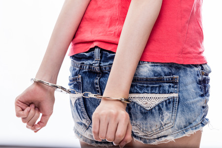 handcuffed hands: Woman with hands handcuffed behind back
