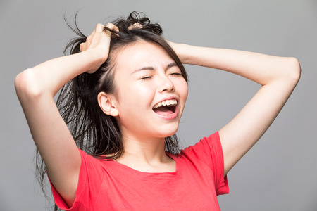 Frustrated and stressed angry Chinese woman pulling her hair with hands