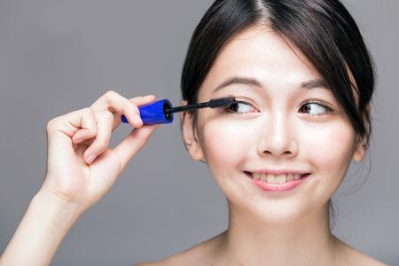 灰色の背景にまつげのマスカラーを置く中国の女性