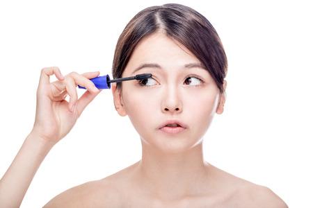 early 20s: Chinese woman putting mascara on eyelashes