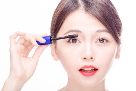 Chinese woman putting mascara on eyelashes