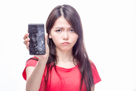 Frowning Chinese woman, OOF,  holding cell phone with cracked screen