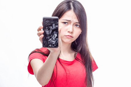 Frowning Chinese woman holding cell phone with cracked screen