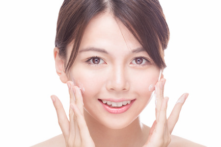 Beautiful Chinese woman applying cream to face. skincare concept Foto de archivo