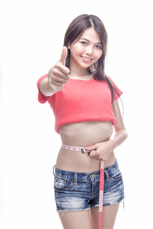 measuring waist: Chinese woman measuring waist with thumb up for successful weight loss