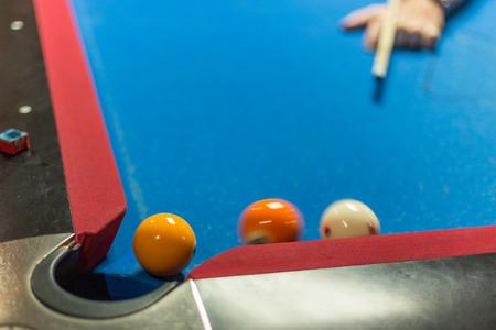 billiards halls: Ball near corner pocket of a pool table, motion blur on balls