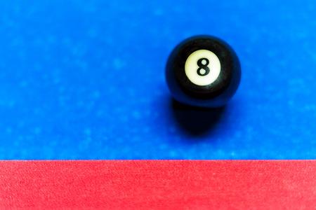 EIght ball near cushion on pool table