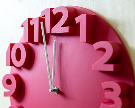 12 oclock: Red clock showing five to midnight on the face