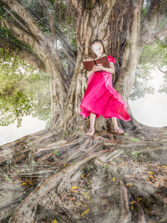 Young child reading glowing book next to a tree Stock Photo