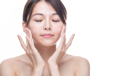 Chinese woman applying cream to face, skincare concept Imagens