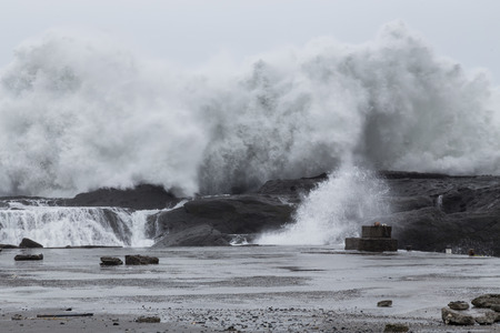 typhoon: Stormy sea with waves crashing on rocks during Typhoon Souledor Stock Photo