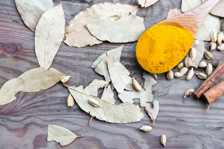 curry powder: Curry powder in spoon on a wooden table with cinnamon sticks Stock Photo