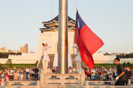 lowering: TAIPEI CITY, TAIWAN - AUGUST 2, 2015: The Honor Guard performing daily Taiwanese flag lowering ceremony in Liberty Square surrounded by an audience, with the Chiang Kai-Shek Memorial Hall in background.