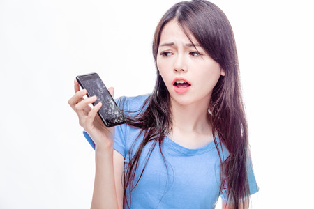 disbelief: Asian woman looking at broken smartphone in disbelief