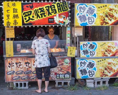 street vendor: NEW TAIPEI CITY, TAIWAN - SEPTEMBER 11, 2015: Street vendor and shopper at Danshui shopping area Editorial