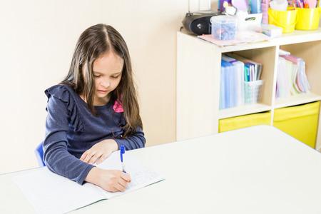 asian american: Asian American schoolgirl in class, writing in book