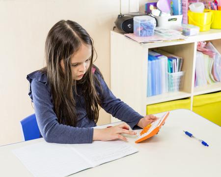 colegiala: Colegiala asiática-americana en clase, utilizando la calculadora