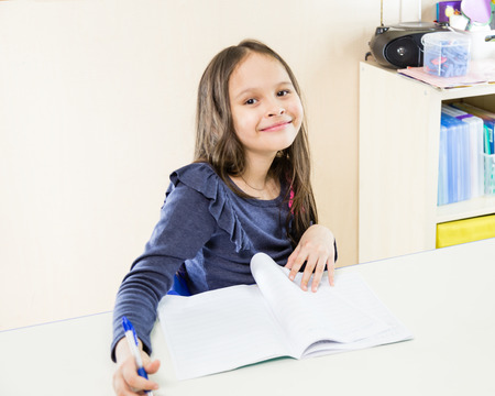 asian american: Asian American schoolgirl in class, smiling and looking at camera