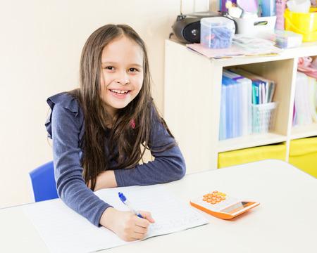 asian american: Asian American schoolgirl in class, using calculator