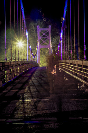 ghostly: Non-descript ghostly male figure walking on bridge, defocused and texture applied Stock Photo