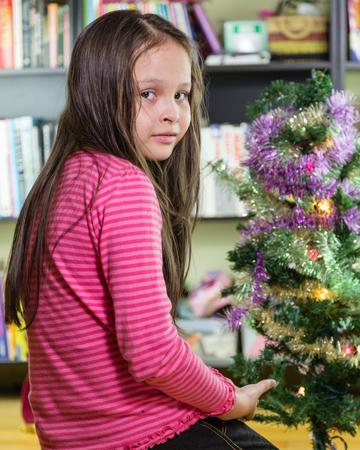 decorating christmas tree: Young girl decorating Christmas tree looking at camera