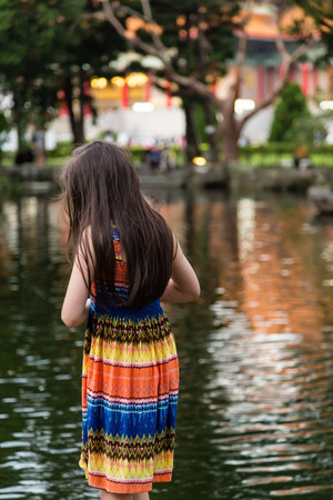 colorful dress: Young girl in colorful dress by lake Stock Photo