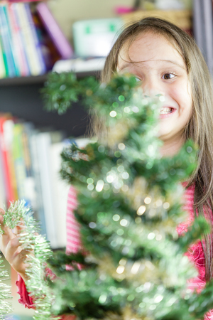 decorating christmas tree: Young girl happily decorating Christmas tree