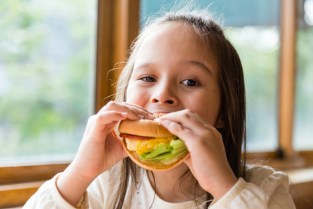 children eating: Asian American girl eating burger