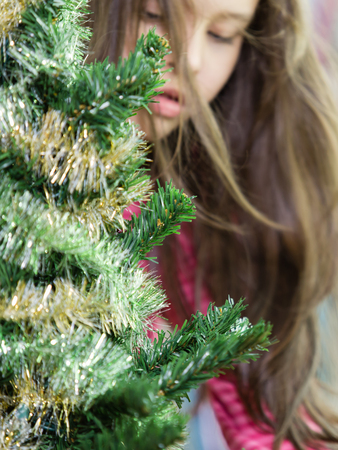 decorating christmas tree: Young girl decorating Christmas tree Stock Photo