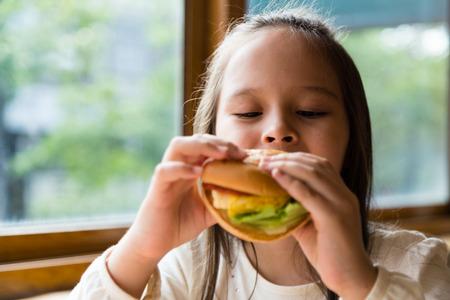 Asian American girl eating burger Stock Photo - 50477291
