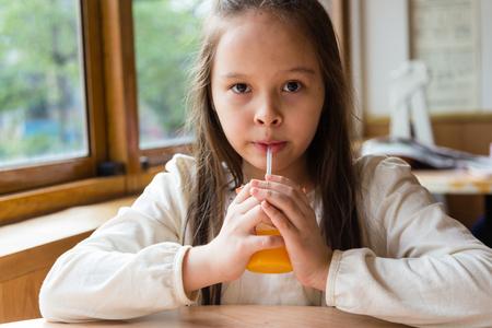 asian american: Asian American girl drinking orange juice Stock Photo
