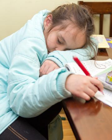 Young schoolgirl falling asleep while doing her homwork Stock Photo
