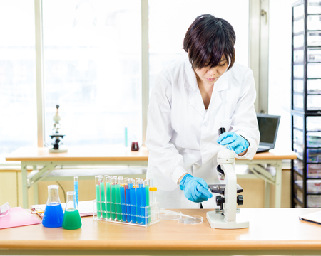 Female Chinese scientist in a laboratory working with microscope