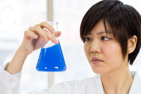 erlenmeyer: Female Chinese scientist looking at erlenmeyer flask
