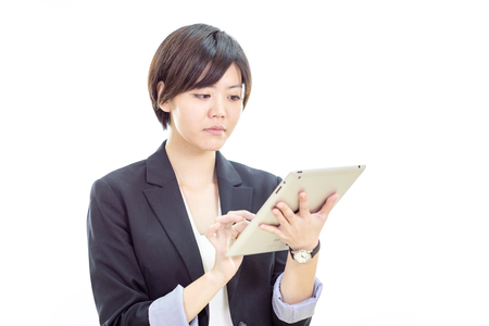 busineswoman: Chinese businesswoman in casual office clothes working on tablet computer